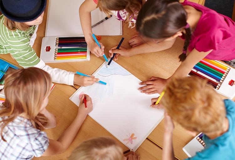 fünf Schulkinder malen gemeinsam an einem Bild an einem großen Tisch.