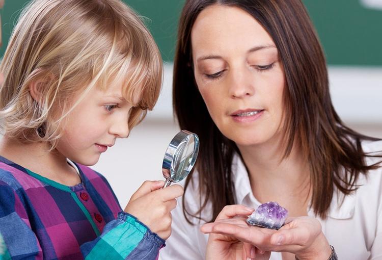Eine Frau zeigt einem Mädchen einen Kristallstein. Das Kind betrachtet ihn mit der Lupe.