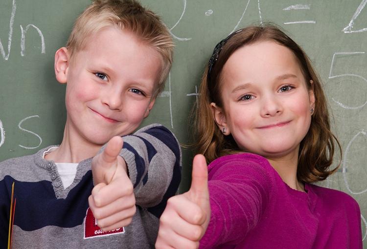 ein Junge und ein Mädchen im Grundschulalter stehen vor einer Schultafel und halten den Daumen hoch.
