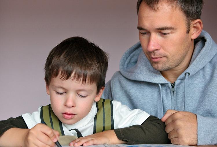 Ein Mann hilft einem kleinen Jungen bei erledigen von Aufgaben in einem Arbeitsheft.