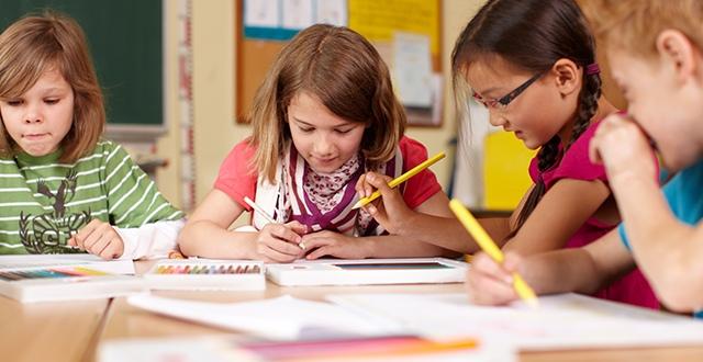 Vier Schulkinder sitzen an einem Tisch im Klassenzimmer und bearbeiten ihre Aufgaben.