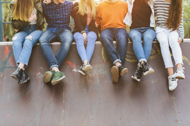 sechs Jugendliche, von denen man die Beine und den Unterkörper erkennt, sitzen auf einer Skater-Wand.