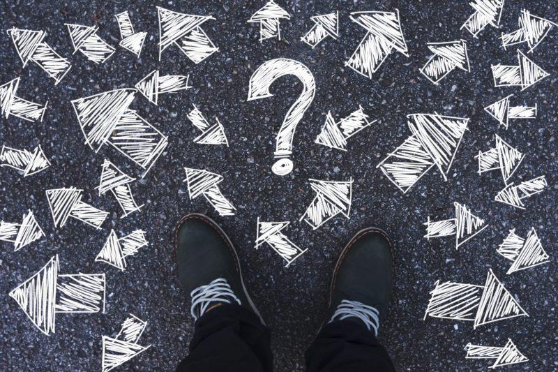 Füße stehen auf dem Asphalt, vor vielen mit Kreide gezeichneten Richtungspfeilen und einem Fragezeichen