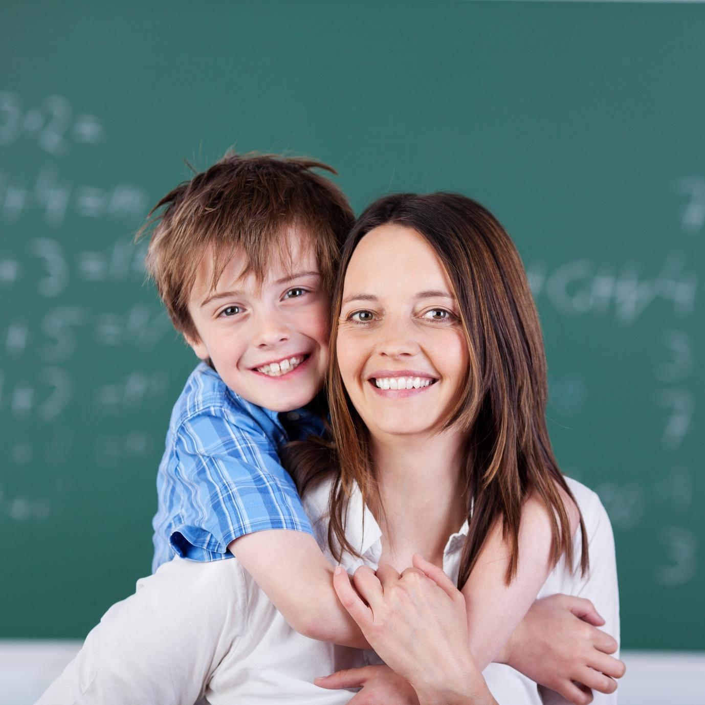 Schüler und erwachsene Frau vor einer Schultafel