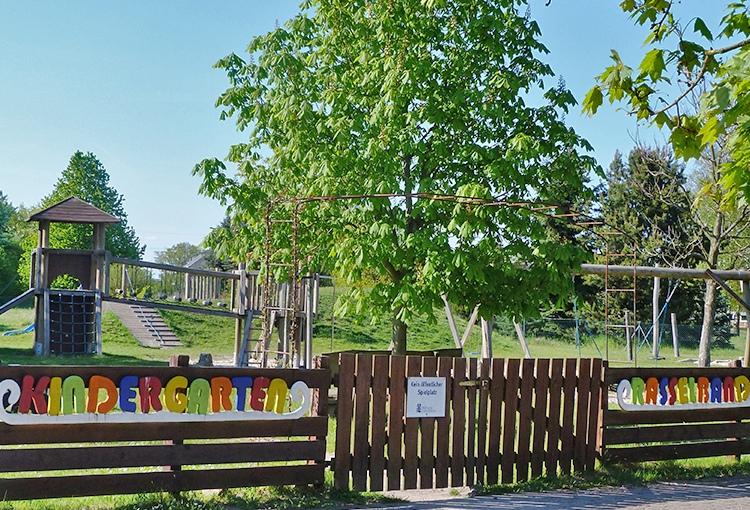 """umzäunter Spielplatz mit Schriftzug """"Kindergarten Rasselbande"""""""